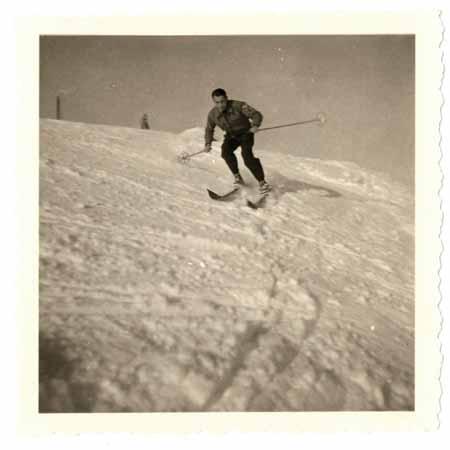 Sportlich abfahrender Skifahrer auf ungewalzter Piste.